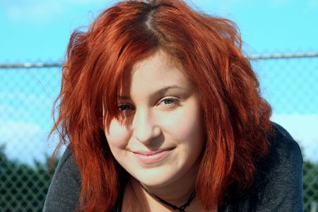 Portrait of smiling contemporary teen girl, taken outdoors.  Horizontal format.