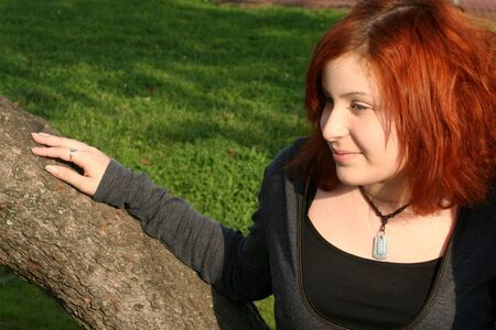 offshoot: Smiling teen girl leaning on a large offshoot of a tree trunk.