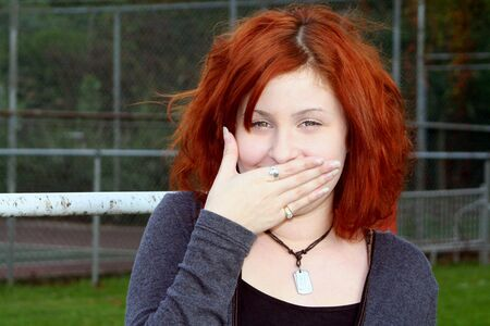 clowning: Laughing teenage girl covering her mouth, taken outdoors at a school playground.