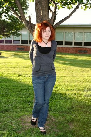 Thoughtful teenage girl standing against a tree on school grounds, looking to her left.