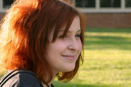 relive: Portrait of a smiling teenage girl in thought on school grounds.  Horizontal format.