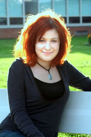 Portrait of a smiling teenage girl sitting on a bench on school grounds.