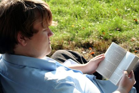 Teenage boy sitting on the ground reading a paperback book.  From a back viewpoint over the models right shoulder, to the side.