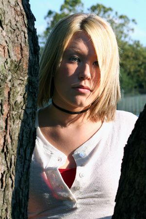 Serious blond young woman, in light and shadows.  Taken outdoors. Stock Photo