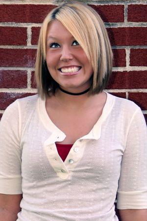 Smiling young woman glancing upward, brick wall as background.