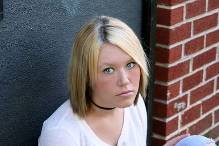 Serious young blond woman, sitting in an exterior doorway.