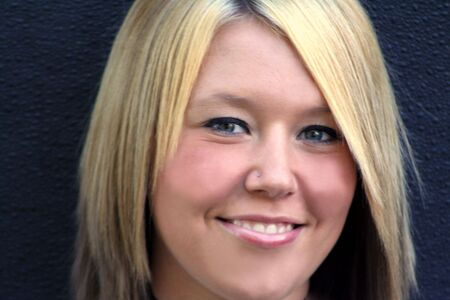 Closeup portrait of a smiling young blond woman, in horizontal format.