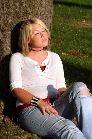 upraised: Young blond woman sitting on the ground against a tree with her eyes closed and her face turned upward toward the sunlight.