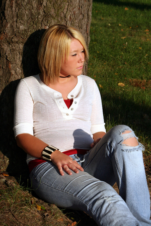 captivating: Serious young woman sitting on the ground leaning against a tree with the sun shining directly on her.