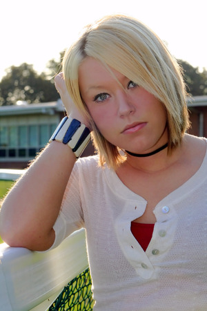 Serious young blond woman leaning her head on her hand on a fence, with a school building in the background. Stock Photo
