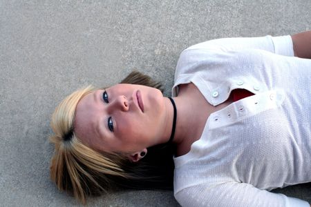 cagey: Young blond woman laying on the ground on a concrete background.