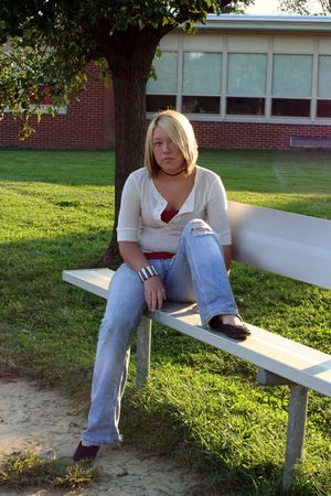 Thoughtful young blond woman, sitting on a bench on school grounds. Imagens - 2632349