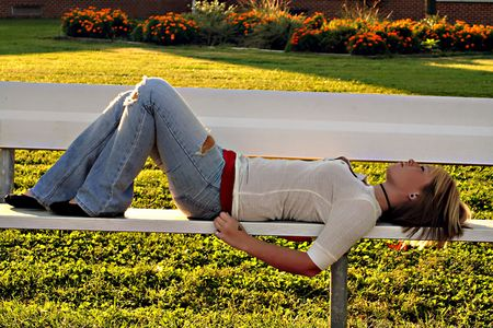 Serious young blond woman lying on a bench in profile on school grounds.