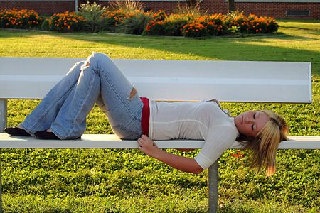 Serious young blond woman lying on a bench on school grounds. Stock Photo