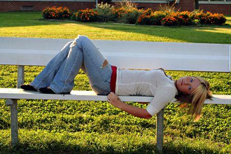 sprawled: Grave joven rubia mujer acostada en un banco en la escuela.