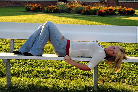 sprawled: Serious young blond woman lying on a bench on school grounds. Stock Photo