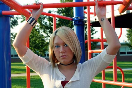 upraised: Serious young woman standing on a school playground, holding onto a bar above her head. Stock Photo