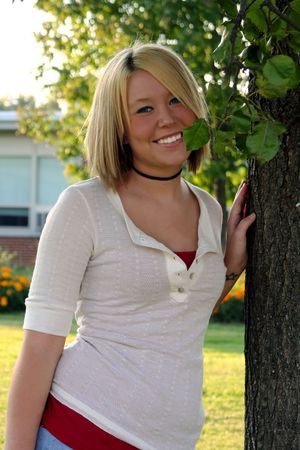 Young blond woman with a shy smile, leaning against a tree.
