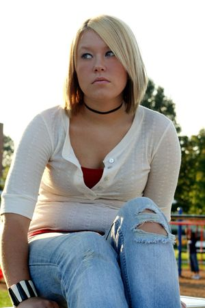 bummed: Serious young blond woman sitting outdoors, looking cautiously to her right.