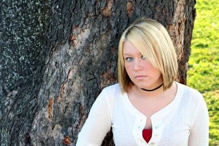 Coy young blond woman standing in front of a large tree. Stok Fotoğraf