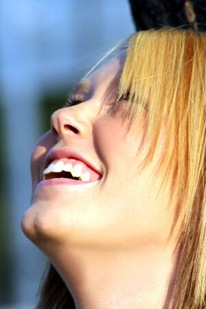Closeup of a smiling young blond woman with her head tilted back.