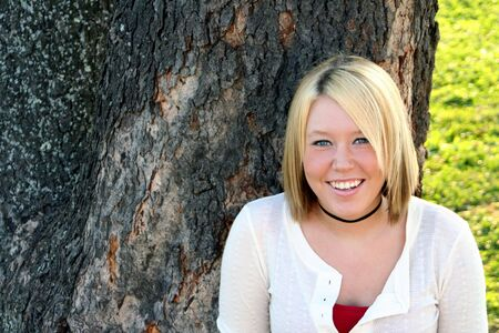 captivating: Smiling young blond woman standing in front of a large tree.