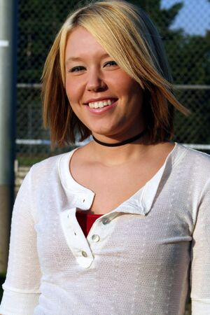 Smiling young blond woman, taken outdoors.