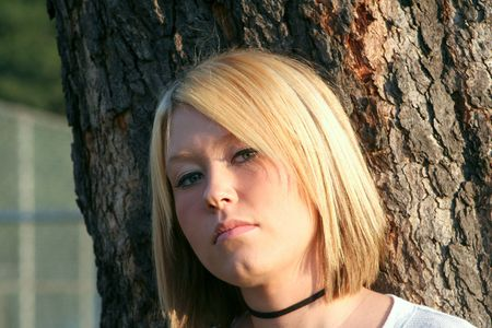 Serious young blond woman with an unsure expression, in front of a large tree outdoors.