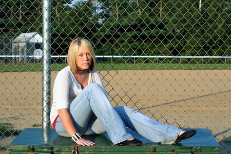 earnest: Serious young woman sitting on a metal equipment box near a fenced baseball field.