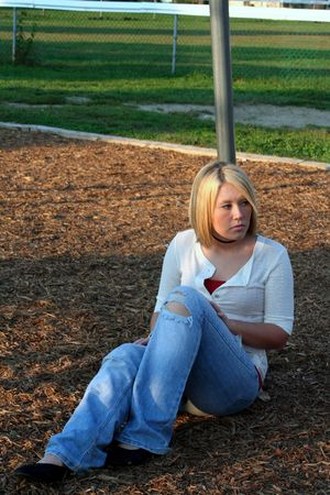 withdrawn: Serious young blond woman sitting on the ground, leaning against a pole of a playground swing set.