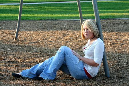 Serious young blond woman sitting on the ground in profile, looking toward the viewer, leaning against the pole of a swing set on a playground.  Imagens