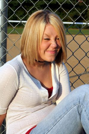 ornery: Smiling young blond woman sitting by a fence and ballfield, her eyes closed and face squinted into a silly face. Stock Photo