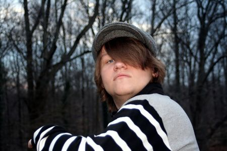 obscuring: Teenage boy wearing a gray cap, peeking out from behind his hair obscuring his left eye.  Taken outdoors. Stock Photo
