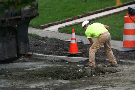 Road worker shoveling broken asphalt at a work site. photo
