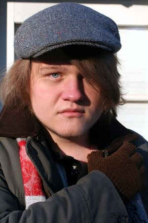 Outdoor portrait of a serious teenage boy in winter. 免版税图像