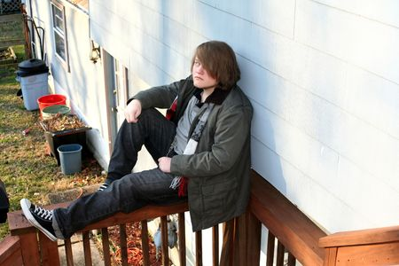Serious teenage boy sitting on a railing, looking upward from behind long hair. photo