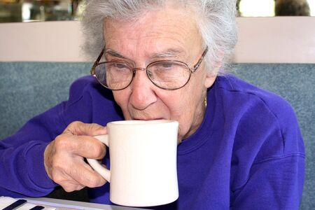 Senior citizen woman drinking from a cup of coffee at a diner. photo