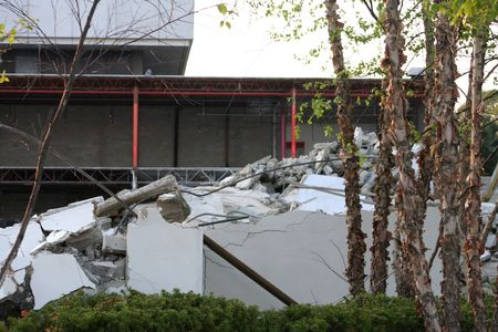 partially: Pile of remnants of a building demolition piled in front of the partially demolished building.