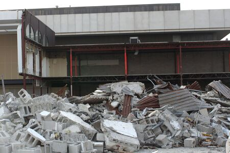 Remnants of a building demolition piled in front of the partially demolished building.