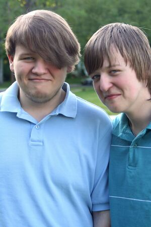 easygoing: Portrait of two smiling teenage brothers outdoors.
