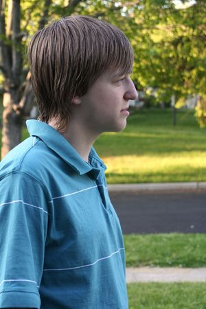 bummed: Profile of a serious teenage boy in an outdoor setting. Stock Photo