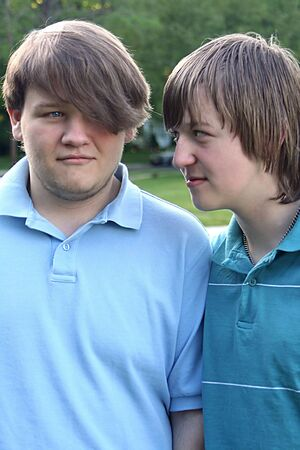 ornery: Portrait of playful teenage brothers outdoors.