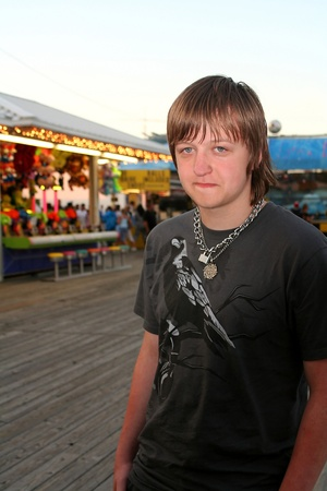 Sad Teen On Festive Boardwalk photo