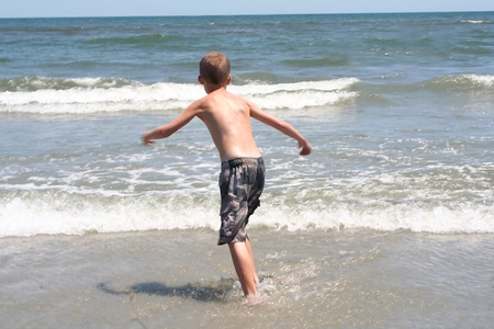 Back view of a 9 year old boy running into the surf at the beach in Wildwood, New Jersey. photo