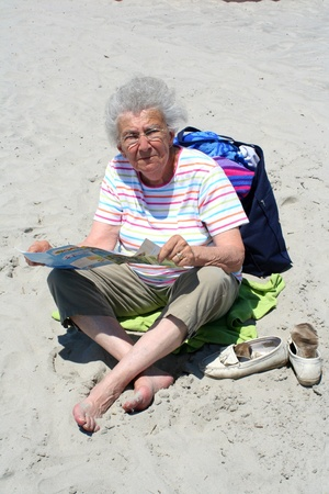 Senior citizen woman sitting on a beach reading a brochure. photo