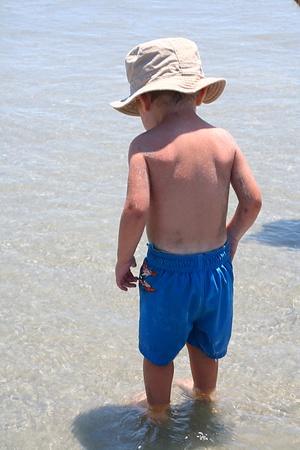 bambini pensierosi: Vista posteriore di un ragazzo bambino indossa un cappello sole, in piedi caviglie nell'acqua dell'oceano.