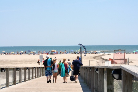 Group of young adults walking down a boardwalk ramp toward the beach in Wildwood, New Jersey. Stock Photo