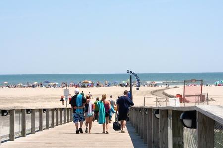 shoreline: Grupo de adultos j�venes que caminaban por una rampa hacia el paseo mar�timo de la playa en Wildwood, New Jersey.