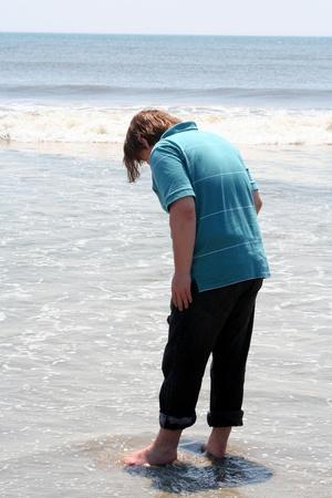 Teen Boy Stepping Into Ocean Surf photo