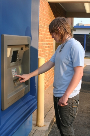 secure payment: Teen Boy Using ATM Stock Photo